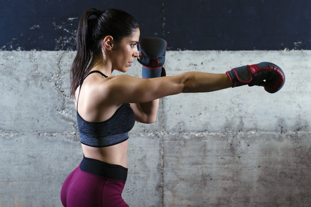 Fitness muscular build woman with boxing gloves exercising in the gym.