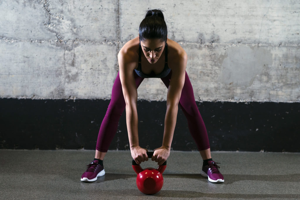 Fitness woman in sports clothes exercising with kettle bell weight in the gym.