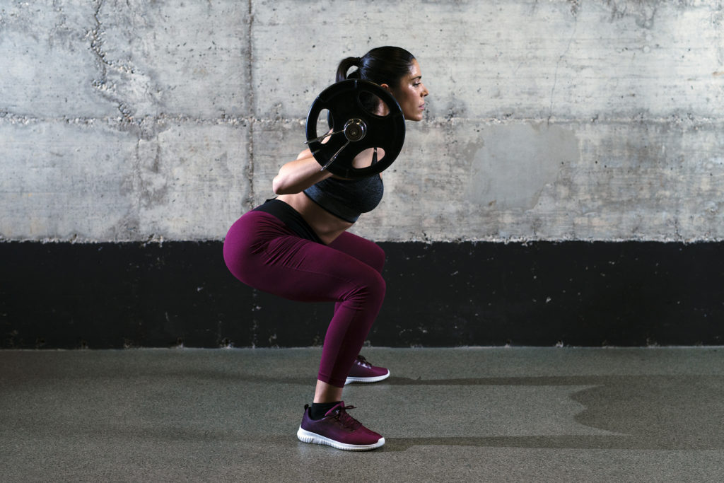 Sporty fitness woman in crouching position doing squats and lifting weight in the gym.